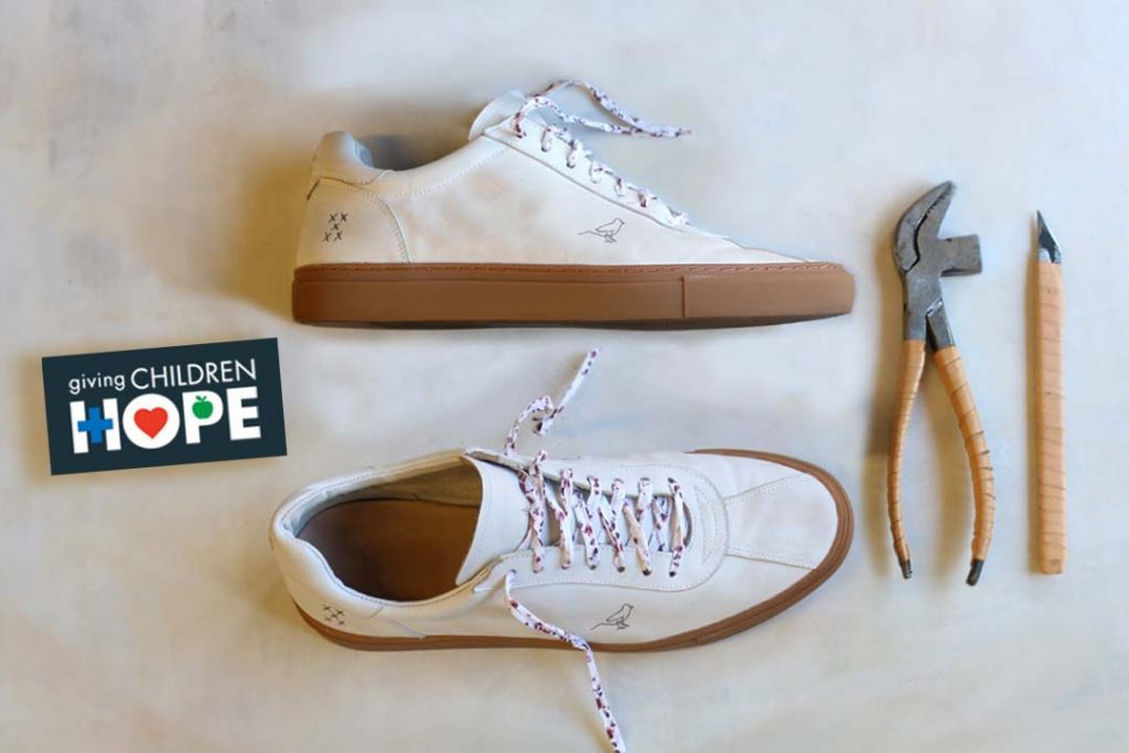 White sneakers with tattoo sitting along side shoe tools